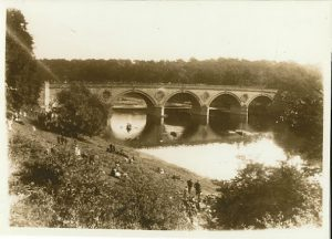 Photograph of Regatta day at Coldstream Bridge. A coble race in progress. The bank on the left is where Jacobs well is. Now overgrown.