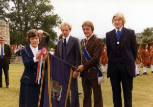 Donald Maxwell getting his colours.Mrs Bell with the honour. Harry Brydon and James bell right and left hand men